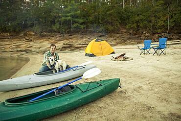 Man and dog with kayak at campsite