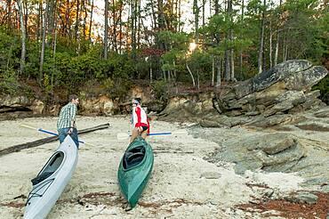 Couple pulling kayaks on rocks