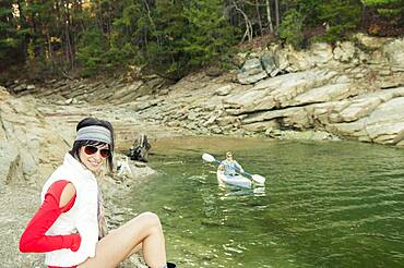 Woman near boyfriend rowing kayak in lake