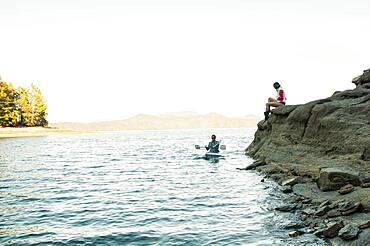 Woman watching boyfriend rowing kayak in lake