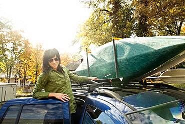 Caucasian woman packing kayak on car