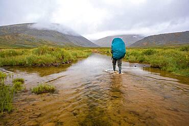 Mari backpacker walking in remote stream
