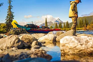 Mari hiker standing on rocks in remote river