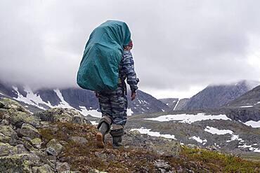 Mari backpacker walking on mountain path