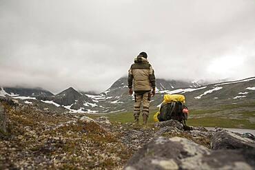 Mari backpacker standing in mountain field