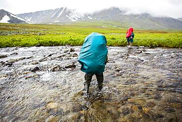 Backpackers crossing remote stream
