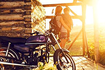 Mother holding son near motorcycle on patio