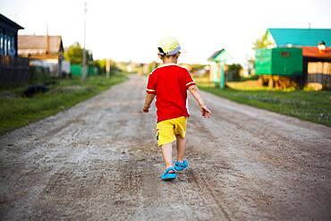 Mari boy walking on dirt path