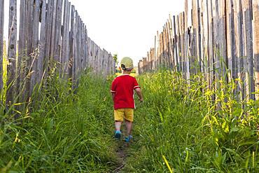 Mari boy walking in grass between fences