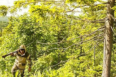 Mari man with gun climbing forest hill