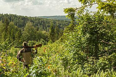 Mari man with gun overlooking rural landscape