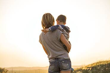 Mother holding son in rural field