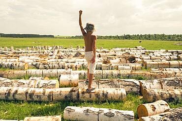 Mari boy standing on logs in rural field