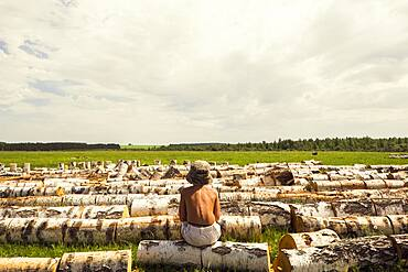 Mari boy sitting on log in rural field