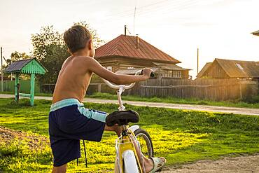 Mari boy riding bicycle
