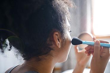 African American woman applying blush to cheek