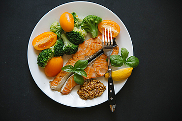 Cooked salmon on plate with broccoli and tomatoes