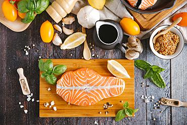 Raw salmon on cutting board with ingredients