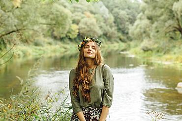 Middle Eastern woman wearing flower crown near river