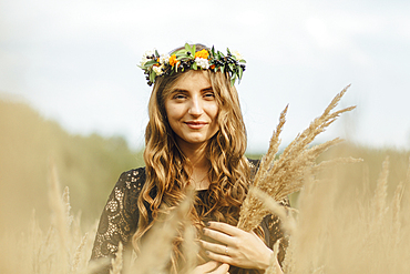 Middle Eastern woman wearing flower crown holding wheat