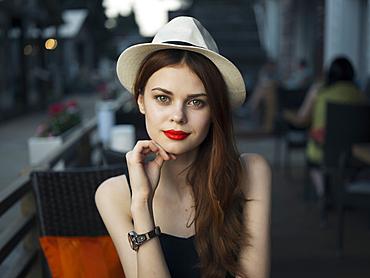 Confident Caucasian woman at sidewalk cafe