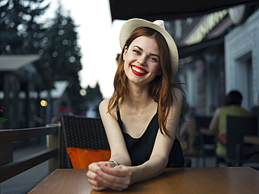 Caucasian woman at sidewalk cafe smiling