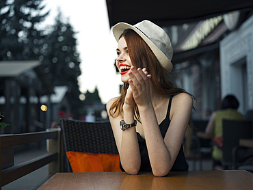 Caucasian woman at sidewalk cafe laughing