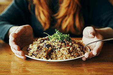 Hands of woman holding a plate of rice