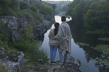 Caucasian couple wrapped in blanket standing on rock admiring river