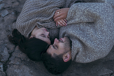 Caucasian couple laying on rock wrapped in blanket