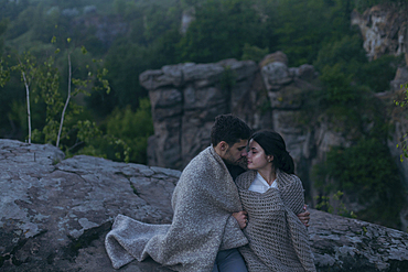 Caucasian couple sitting on rock wrapped in blanket