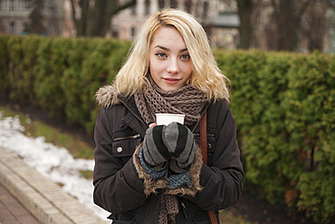 Caucasian woman warming hands on cup of coffee