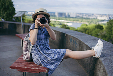 Caucasian woman sitting on bench photographing with camera