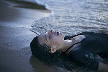 Caucasian woman laying on beach in waves