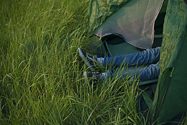 Legs of Caucasian man laying in tent