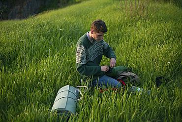 Caucasian hiker kneeling in grass