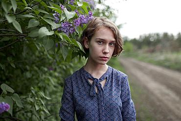 Pensive Caucasian woman standing near flowers