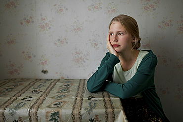 Portrait of pensive Caucasian woman leaning on table