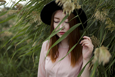 Pensive Asian woman standing in field of tall grass