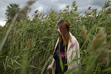 Asian woman standing in field of tall grass