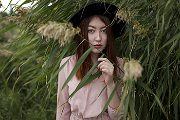 Asian woman standing in foliage