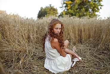 Caucasian girl sitting in wheat