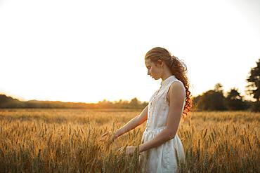 Caucasian girl standing in field of wheat