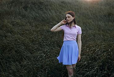 Caucasian girl standing in windy field