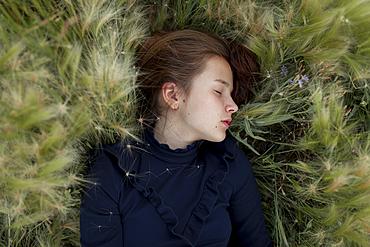 Caucasian girl laying in field