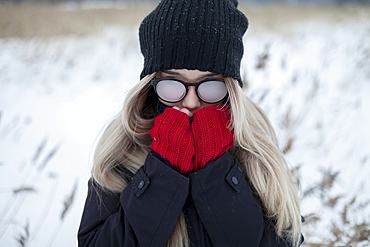 Cold Asian girl wearing a hat and eyeglasses in winter