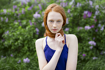 Caucasian teenage girl wrapping hair around neck
