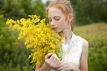 Caucasian girl smelling wildflowers