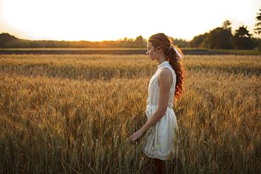 Pensive Caucasian girl standing in field of wheat