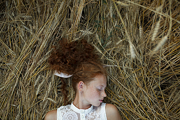 Serious Caucasian girl with freckles laying in wheat